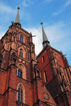 bottom up view of two brick towers of the gothic cathedral of Saint John the Baptist in Ostrow Tumski Wroclaw, Poland Standard-Bild