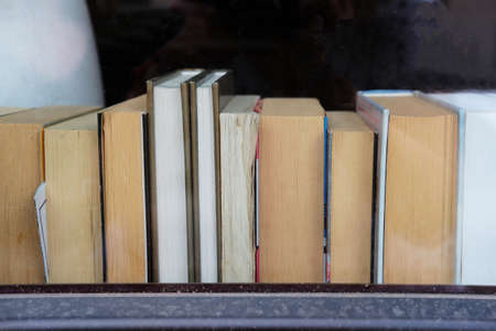 Old books on a windowsill of a cafe. Concept photo illustrating intellgence and learning. Copy space Banque d'images