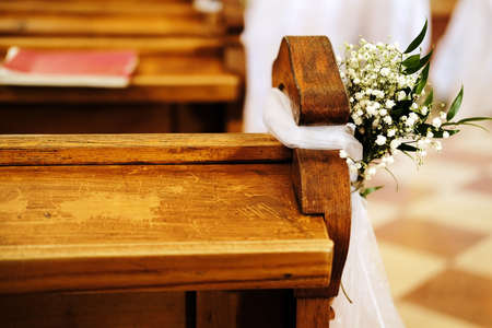 benches in church decorated with white flowers and fabric for a wedding