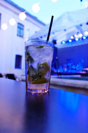 Vertical photo of mohito in a glass on a table at an open air pub in an old european city. Background with blue light
