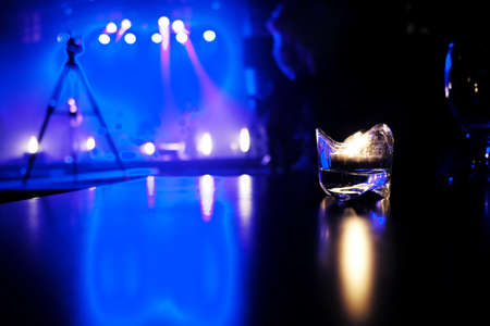 candle lit on a table in a cafe with blue lit stage in the background.Waiting for a concert on a cold september evening. Standard-Bild