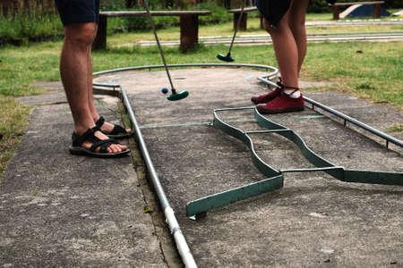 Man and woman playing miniature golf in summer Standard-Bild
