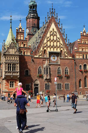 Wroclaw, Poland. 08/23/2020 Verttcal photo of people walking in the Market Square with the historic town house in the background. Editorial