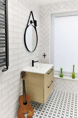 Modern white bathroom washbasin with black tap, round mirror and black and white floor tiles and an old guitar as a decoration
