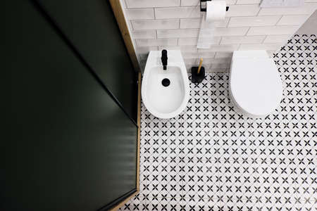 Top down view of a modern bathroom with dark green closet and retro retro style black and white floor tiles Standard-Bild