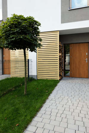 Entrance to a modern terraced house with green lawn, maple tree and car parked on the driveway Foto de archivo
