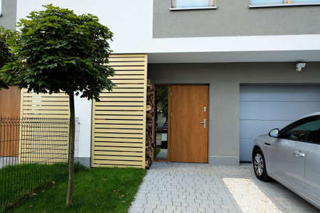 Entrance to a modern terraced house with green lawn, maple tree and car parked on the driveway