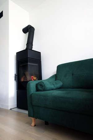 Modern scandinavian living room with green sofa and a modern freestanding contemporary fireplace Standard-Bild