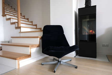 Modern scandinavian living room with navy blue armchair, staircase and a modern freestanding contemporary fireplace.