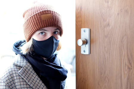 sad and worried teenage girl wearing a black protenctive sanitary mask enters a house during second lockdown in coronavirus (Covid-19) pandemic