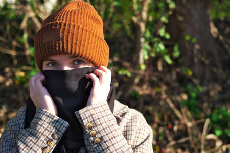 teenage girl covers her mouth and nose with a scarf as a protective against Convid-19 virus in the age of pandemic
