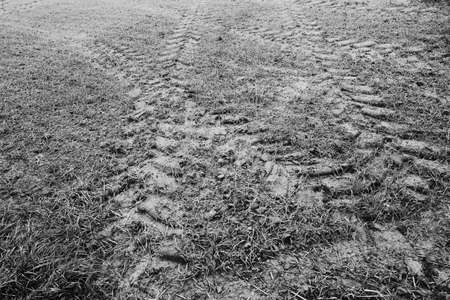 Natural background with tractor tire tracks in wet muddy field