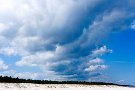 blue sky and dramatic clouds over sandy beach