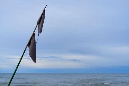 old gray fishing flag against calm blue sea