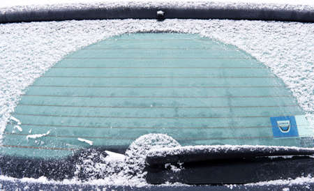 close-up of frosted car rear with frozen windshield and wiper on a snowy winter morning Standard-Bild