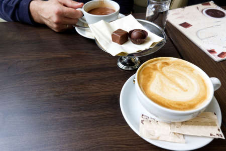 man drinking hot chocolate, cappucino and eating pralines in a cafe Standard-Bild