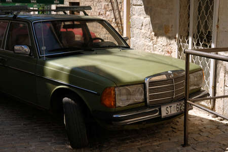 Kastela, Croatia. August 17 2021. Classic green Mercedes Benz 1W123 parked in the narrow street of the old town
