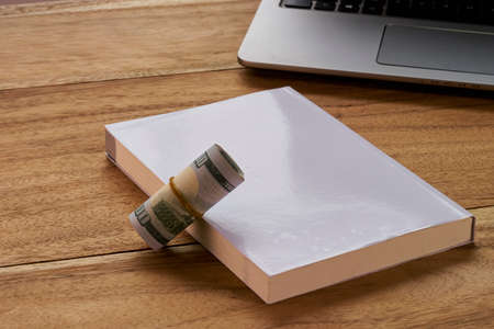 money roll: Book with money roll and Laptop on wood background layout