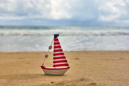 Small toy sailing yacht on the beach Stock Photo