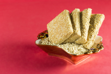 ceremic: Gajak or an indian sweet dish made with Sesame seed and jaggery served in a ceramic bowl on a red background