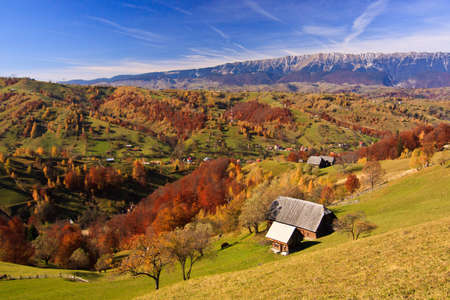 Mountain autumn landscape with colorful forest and traditional houses