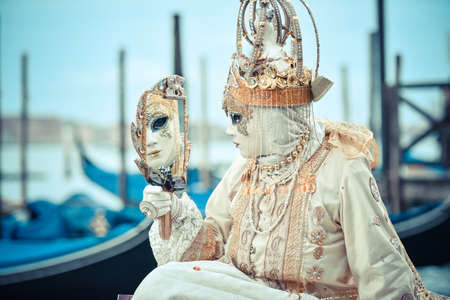 Beautifull Venetian masked model from the Venice Carnival 2015 with Gondolas in the background