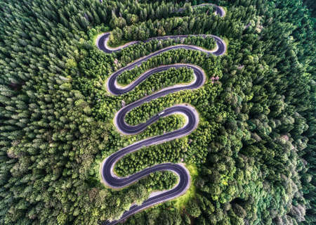 Curvy road from the high mountain pass in Transalpina, Romania. Great road trip trough the dense woods. Aerial view. Foto de archivo