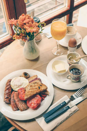 eggs and bacon: English Breakfast with sausages, eggs, bacon, tomato and orange juice Stock Photo