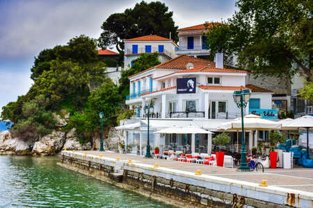 Skiathos town greek tavern by the sea with fishing boat and blue water