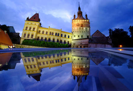 inhabited: Sighisoara by night. Old Clock Tower reflection. Transylvania top tourist destination in Romania. Oldest medieval inhabited walled city in Europe. Editorial