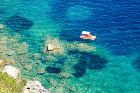 blue waters: Diver doing snorkeling in the blue waters in Greece. Corfu island Kerkyra. Solo divers in the water. Stock Photo