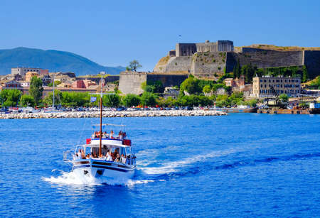 Boat sailing in daily trips around Corfu island with the old venetian fortress walls in the background.