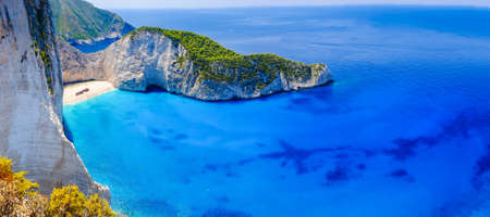 Zakynthos shipwreck beach. Navagio Bay panorama with boats and clear waters. Touristic attraction.