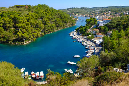 Paxos island grand canal with boats anchored and traditional houses. Important touristic attraction in Greece, near Corfu Island Stock Photo