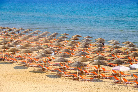 sunbeds: Beach umbrella and sunbeds on the sandy beach in Greece