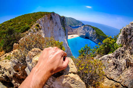 tourist spot: Tourist looking at Navagio Shipwreck panoramic scenic view spot in Zakynthos island Greece. Artistic interpretation. Focus on hand.
