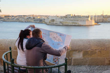 Couple in Valleta reading a map at sunset in the old town citadel near the harbour. Famous tourist attraction Stock Photo