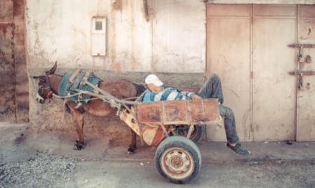 street vendor: MARRAKECH, MOROCCO, JUNE 2016: Street vendor sleeping in his cariage