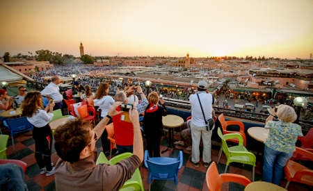 MARRAKECH, MAROKKO, JUNI 2016: toeristen fotograferen bij zonsondergang over Jama el-Fna markt. Belangrijke toeristische attractie