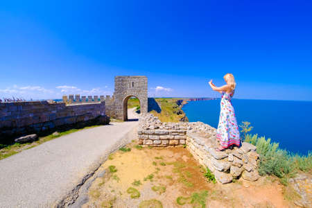 horison: Woman taking pictures at Cape Kaliakra, Bulgaria, Black Sea. Old abandoned fortress by the sea. Important tourist attraction.