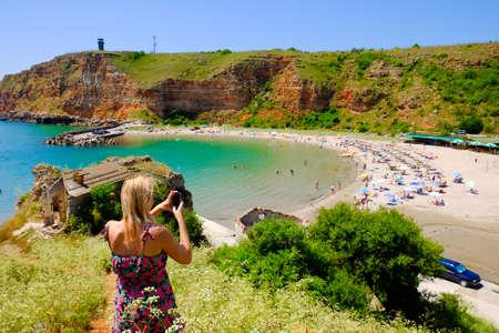 horison: Blonde woman taking pictures at Bolata bay, Bulgaria, Black Sea. Famous beach near Cape Kaliakra. Important tourist attraction. Stock Photo