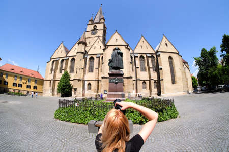 Tourist visiting Sibiu Romania in Transylvania. Old Catholic Cathedral in the main town square.