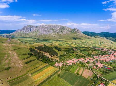 Aerial view of Costesti Village in Apuseni Romania withh Rimetea Piatra Secuiului Mountain in the back