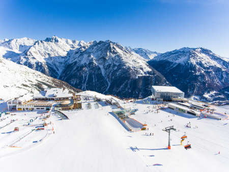 Ski resort in the Alps with ski lift and people skiing on the slope