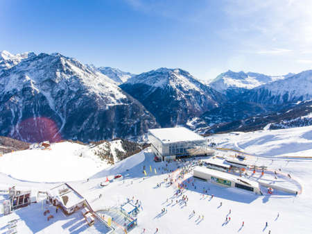 Skiing in the alps. Aerial view over the ski slope with ski lift and gondola visible