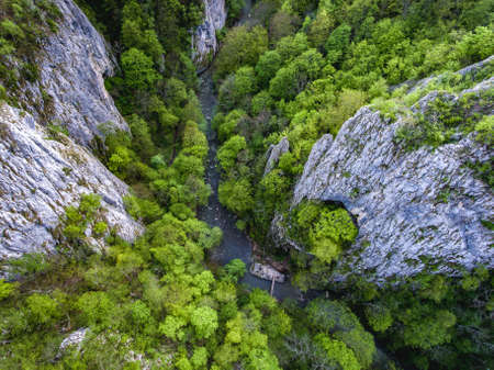 Varghisului Gorges in Covasna and Harghita county, Transylvania, Romania. Entrance to the three caves visible. Aerial view from a drone.