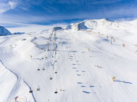 Ski in the Alps with ski lift and people skiing on the slope. Aerial view