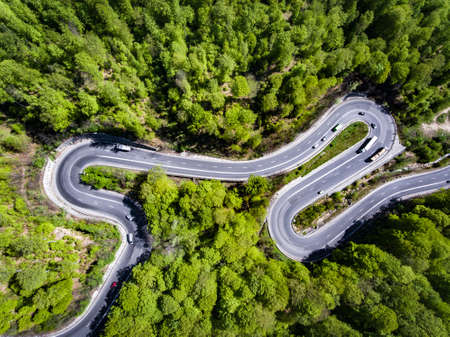 Cars on winding road trough the forest, Transfagarasan, Romania