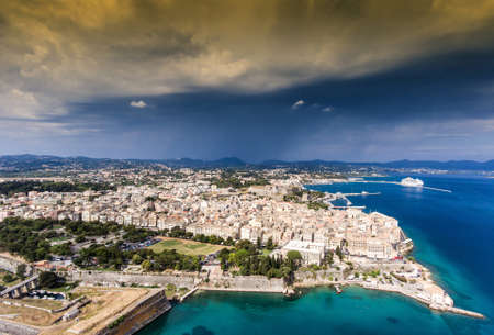 Corfu old city, aerial view, with venetian fortress on the left and the old fortress visibile in the back. Dramatic weather.