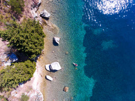 ionian: Young woman floating and swimming in beautiful ethereal natural sea, aerial view
